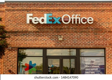 Charlotte, NC/USA - August 7, 2019: Exterior view of Fedex Office facade showing reddish brown brick building with blue and white brand letters and glass windows and doors with colorful logo.