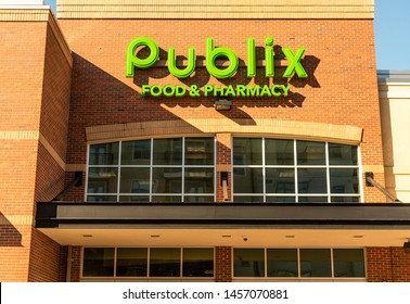 Charlotte, NC/USA - June 20, 2019: Medium exterior view of facade of Publix brand/logo in bright light green letters mounted on reddish brick building with windows below, sunlight, and shadow.