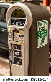 Charlotte, NC/USA - May 10, 2019:  Closeup of medium grey and silver metal uptown Charlotte parking meter curbside along the street with signs, instructions, buttons and a screen.  City budget concept