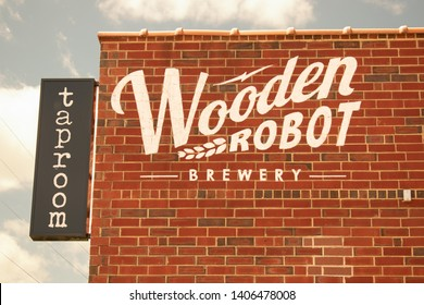 "Charlotte, NC/USA - May 10, 2019: Exterior view of logo of ""Wooden Robot Brewery"" and ""Taproom"" sign on front and side of their red brick building in white letters showing some blue sky with clouds."