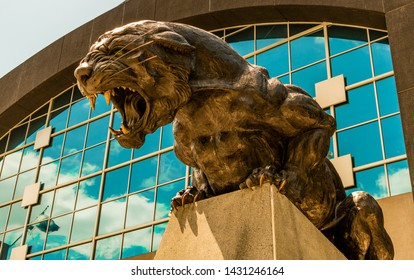 Charlotte, NC/USA - May 14, 2019:  Medium closeup of panther statue, symbol for Carolina Panthers football team outside entrance to Bank of America Stadium with Panthers blue reflection in windows.