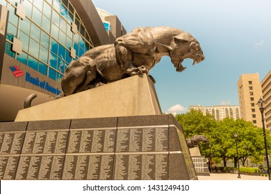 Charlotte, NC/USA - May 14, 2019:  Long profile shot of black panther sculpture outside entrance to Bank of America Stadium with medium blue reflections in windows, sky, pedestal, buildings, BofA logo