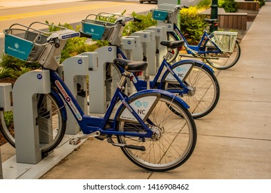 "Charlotte, NC/USA - May 26, 2019: Medium shot of a row of blue ""Atrium Health"" rental bicycles in bike racks on the side of a sidewalk.  Green environment, health, fitness and lifestyle concepts."