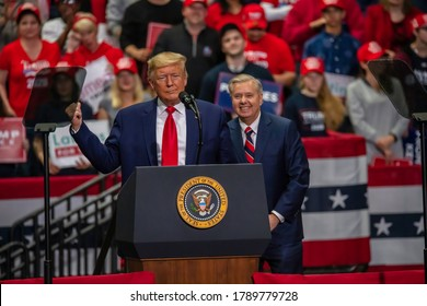 Charlotte, North Carolina - 2 March 2020: Senator Lindsey Graham smiles behind President Trump at the rally in the Bojangle's Coliseum