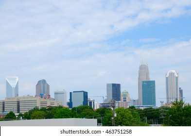 Charlotte, North Carolina, city buildings skyline cityscape in the summer with green trees in foreground.