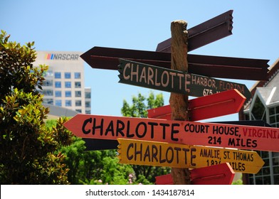"""Charlotte, North Carolina / USA - June 14, 2019: A """"Charlotte"""" directional sign sculpture on """"The Green"""" in Uptown Charlotte seemingly points the the sign of the NASCAR museum in the far distance.."""
