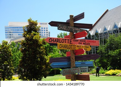 """Charlotte, North Carolina / USA - June 14, 2019: A """"Charlotte"""" directional sign sculpture on """"The Green"""" in Uptown Charlotte seemingly points the the sign of the NASCAR Hall of Fame in the distance."""