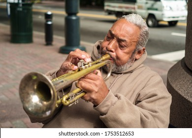 Charlotte, North Carolina USA - October 10, 2013:  Senior street performer playing blues style music on the trumpet in the uptown financial district.