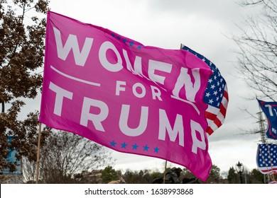 CHARLOTTE, NORTH CAROLINA/USA - February 7, 2020: Women for Trump flag flies in the stiff wind awaiting Presdient Donald Trump's visit to Charlotte, North Carolina on February 7, 2020