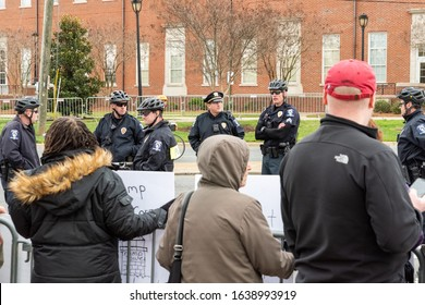 CHARLOTTE, NORTH CAROLINA/USA - February 7, 2020: Police officers watch a small group of quiet demonstrators awaiting President Donald Trump's arrival in Charlotte, North Carolina on February 7, 2020