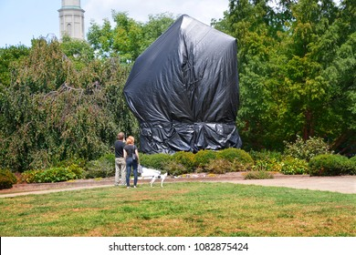CHARLOTTESVILLE, VA–August 25, 2017: A couple stand in front of the tarp shrouded statue of Robert E. Lee in a Charlottesville park where Civil War statues have become a point of contention.