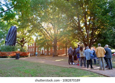 CHARLOTTESVILLE, VA–October 25, 2017: A group discusses events near the tarp shrouded statue of Stonewall Jackson in a Charlottesville park where Civil War statues have become a point of contention.