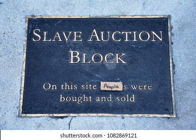CHARLOTTESVILLE, VA–August 25, 2017: A plaque on the ground marks the spot where a slave block once stood. A memorial in sharp contrast to the nearby imposing statue of Stonewall Jackson.