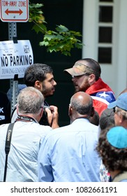 CHARLOTTESVILLE, VA–July 8, 2017: A counter protester and a KKK member confront each other on the street before members of a North Carolina KKK group arrive to rally in a local park.