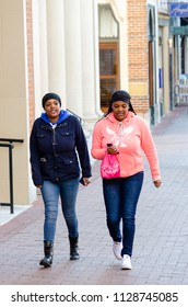Charlottesville, USA - January 10, 2015: Two twin sisters, women, walking in downtown Main Street mall in Virginia with one woman holding kid, baby, toddler, child in arms, hands