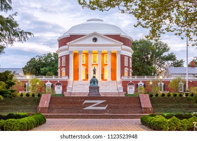 Charlottesville, USA - September 16, 2017: The Rotunda at the University of Virginia at dusk with Thomas Jefferson Statue in the foreground