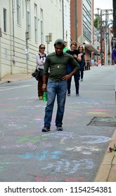 CHARLOTTESVILLE, VA – Aug 11, 2018: Residents view chalked messages left at the site where Heather Heyer was killed on the one-year anniversary of a rally that turned violent.