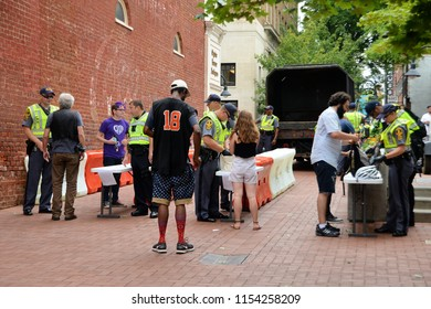 CHARLOTTESVILLE, VA – Aug 11, 2018: Police check bags at an entry point in Charlottesville on the one-year anniversary of a rally that turned violent.