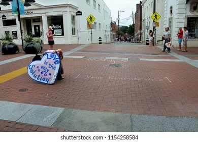 CHARLOTTESVILLE, VA – Aug 11, 2018: A woman chalks a message near the site where Heather Heyer was killed, on the one-year anniversary of a rally that turned violent.