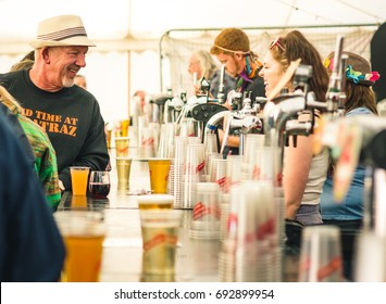 Charlton Park, UK - July 27 2017: Customer talking to bar staff in the beer tent at the Womad Festival in Charlton Park.
