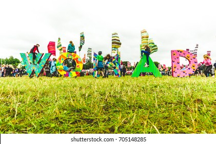 Charlton Park, UK - July 28 2017: Children climbing and sitting on one of the Womad signs at Womad Festival at Charlton Park.