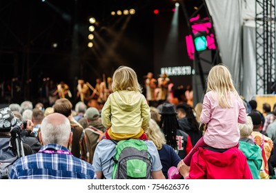 Charlton Park, UK - July 28, 2017: Children sitting on shoulders watching a band at Womad Festival in Charlton Park.
