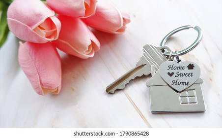 Charm metal house and heart shaped keychains, engraved with word HOME SWEET HOME, on marble table with pink flower. The concept of warm welcome to customers for real estate agent.
