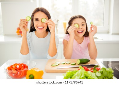Charming adorable attractive beautiful caucasian kind young laughing mum and her small little offspring daughter having fun, cover eyes with cut cucumber in light kitchen