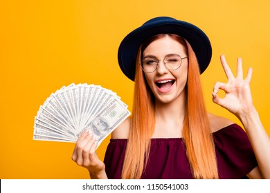 Charming and adorable young woman in hat and glasses looks at camera, wink and show ok sign with lot of money in the hands isolated on yellow background