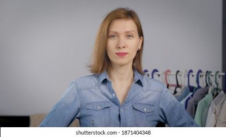 charming adult woman is standing in room of flat and looking at camera calmly, hungers with clothes are behind her