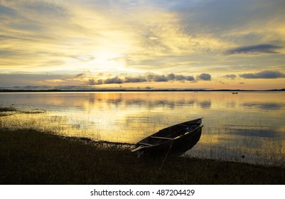 Charming African sunset. A Lake in the evils with a beached boat near the shore. Africa, Mali.