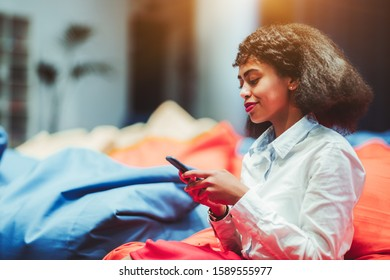 A charming African-American businesswoman is relaxing on a red cushion in a lounge zone of an office and using her smartphone; cheerful biracial woman entrepreneur with a cellphone in a chillout area