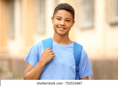 Charming African-American teenager with backpack outdoors