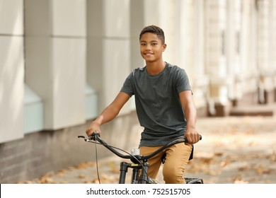 Charming African-American teenager riding bicycle on city street