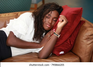 Charming African-American woman in elegant clothes smiling while having nap on comfortable sofa.