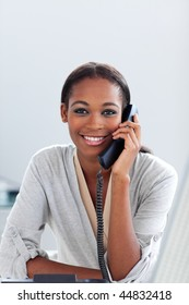 Charming Afro-american businesswoman talking on a phone at her desk