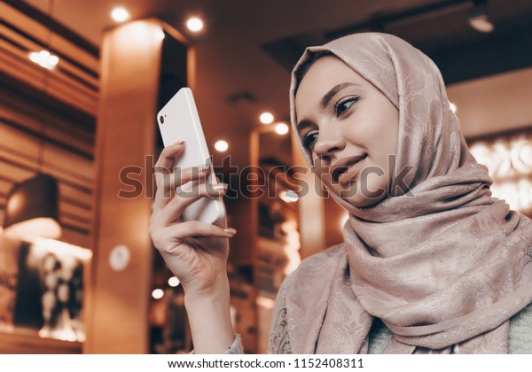 charming Arab girl in hijab looks into her smartphone, waits for food in a restaurant