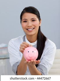 Charming asian businesswoman saving money in a piggybank in the office