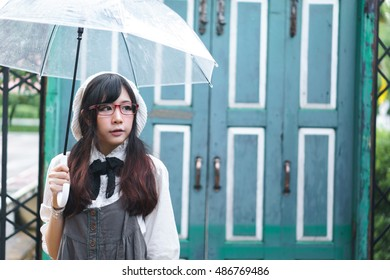 Charming Asian girl with umbrella in raining day