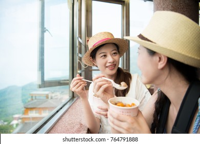 charming Asian girls eating famous yam taro balls on top hill of Jiu Fen of Taipei city Taiwan.