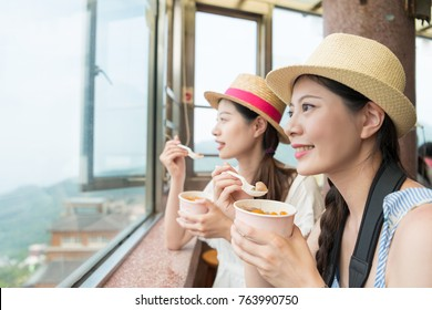 charming Asian girls enjoy the view of the top hill of Jiufen of Taipei city Taiwan. Eating famous yam taro balls for snacking.