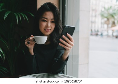 Charming asian hipster girl wearing stylish clothes chatting online by a mobile phone while sitting in a modern city coffee shop on a weekend day. Student girl watching videos on a smartphone.