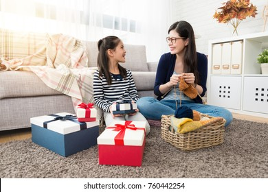 charming Asian mother and her daughter knitting together for the holiday even gift with many boxes sitting on floor of the living room at home.