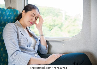 charming Asian office woman feel headache painful on her business train travel journey sitting on her seat.