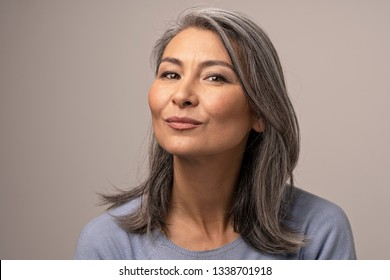 Charming Asian Woman With Grey Hair With Delicate Smile. Pretty Middle-Aged Woman Making Duck Face While Smiling. Portrait.