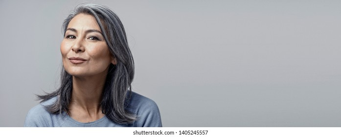 Charming Asian Woman With Grey Hair With Delicate Smile. Portrait Of Pretty Middle-Aged Woman Making Duck Face While Smiling.