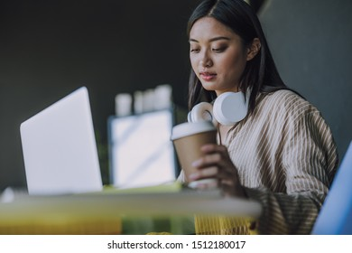 Charming Asian woman having coffee break in office. Leisure time concept