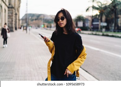 Charming asian woman in sunglasses wearing blank black t-shirt and yellow leather jacket reading messages on a mobile phone while standing on a blurred city background. Hipster girl holding smartphone