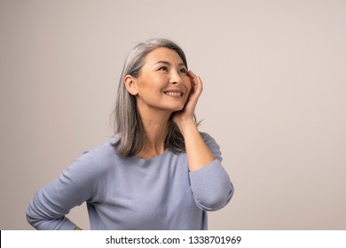 Charming Asian Woman Touches Her Cheek With Hand And Smiles While Looking Up. Smiling Middle-Aged Woman Smiling And Delicately Touching Her Face While Looking Up. Studio Photoshoot. Portrait.