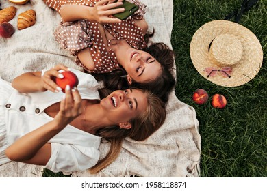 Charming attractive blonde and brunette girls in summer dresses lay on linen rug and have picnic. Cool woman in polka dot dress holds phone. - Shutterstock ID 1958118874